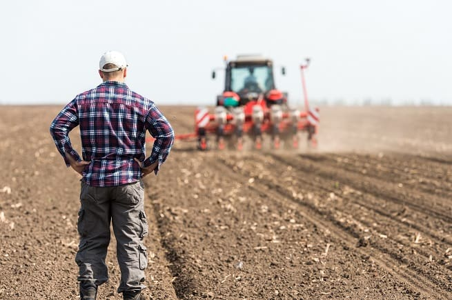 Farmer watching plough in field | Farm Safety Advice for Farm Safety Week