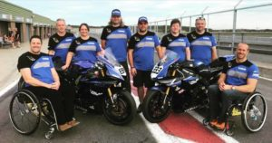 Becci Ashfield of Hudgell Solicitors standing with the Talan Racing motorcycle team