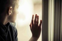 Sad Boy Looking Outside While Holding Glass Window