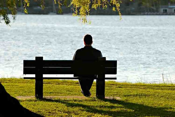 Man alone looking sat on bench