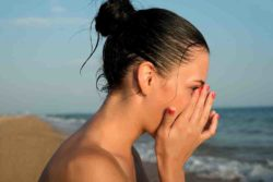 young woman on beach feeling Ill