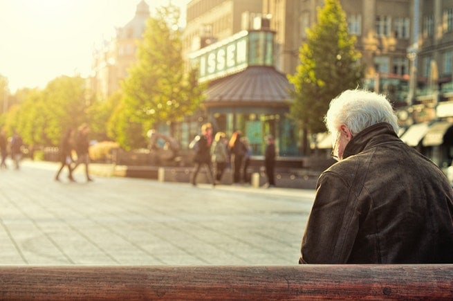 Elderly man sitting on bench | Elderly abuse soars | Hudgell Solicitors