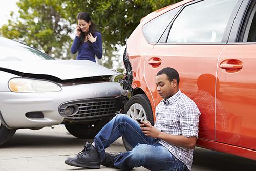 man sat next to car after crash