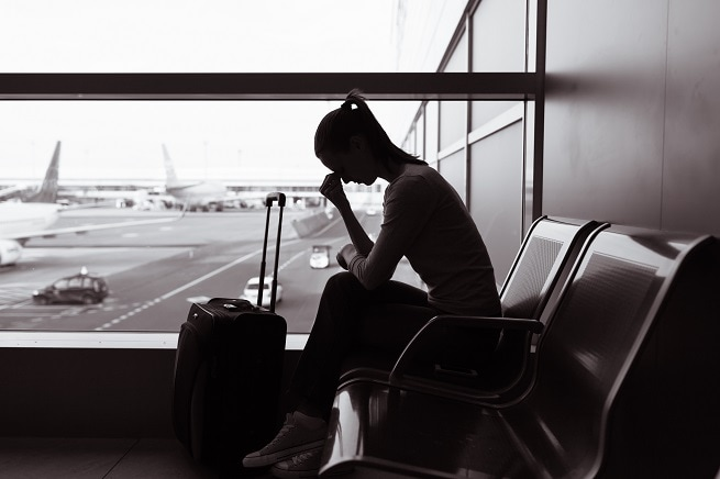 Sad woman sitting at airport feeling unhappy | Where to find holiday illness claims advice