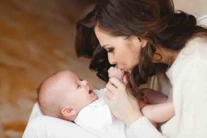 woman kissing baby hands